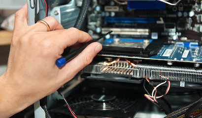 Male hand,  holding a precision screwdriver in front of an open computer. Focus on the fingers holding the screwdriver
