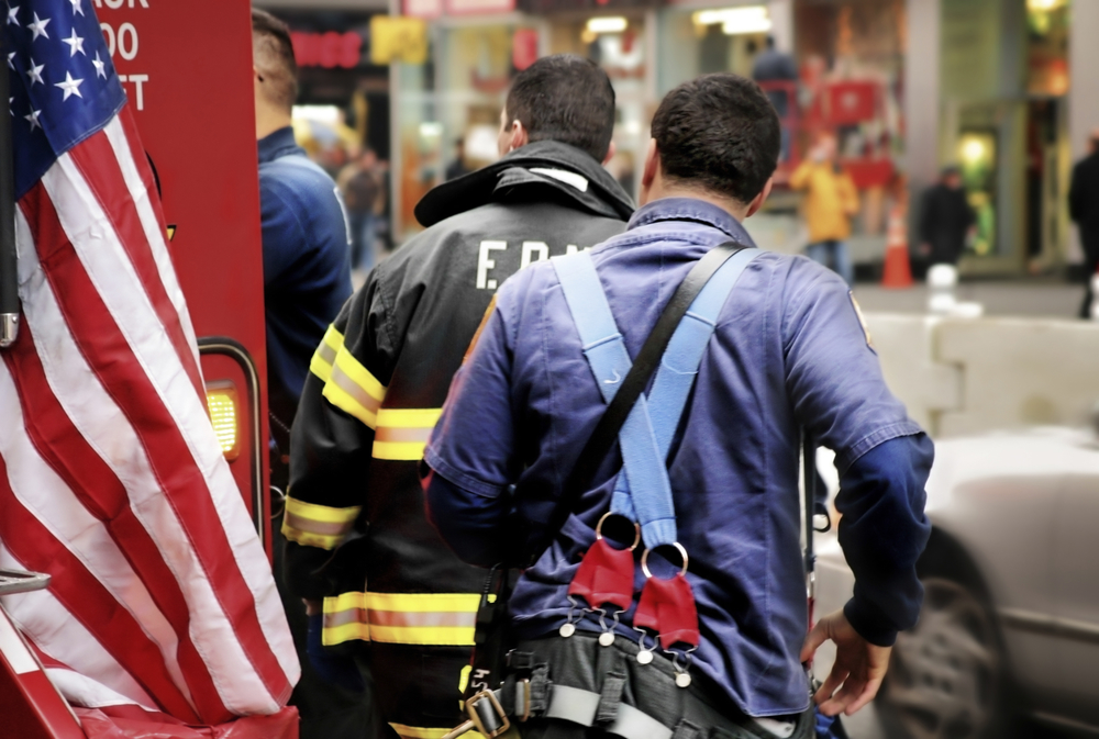 fire fighters with an ambulance and an American flag in chaotic New York City